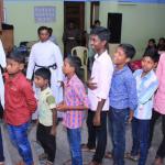 Children in BFMs Sunday School Wait Their Turn To Receive School Supplies