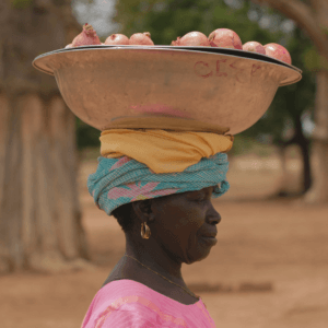 woman proudly carries her goods to market