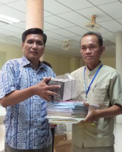 Ministry leader Mony Mok (left) hands teaching materials over to a church planter to use in his short-term training events in his region.