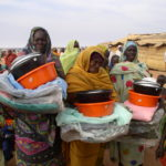 SUAI Darfur women receive relief supplies at a refugee camp Jan 2005