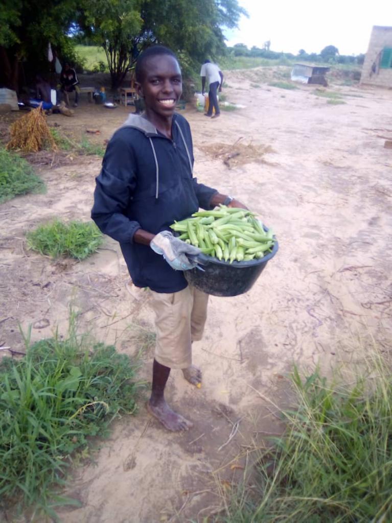 Man holding basket of Okra smiling at camera
