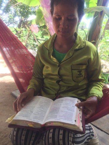 Woman reading a Bible on a hammock