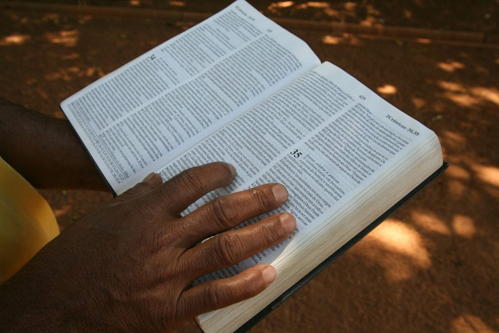 close up of hand on open Bible