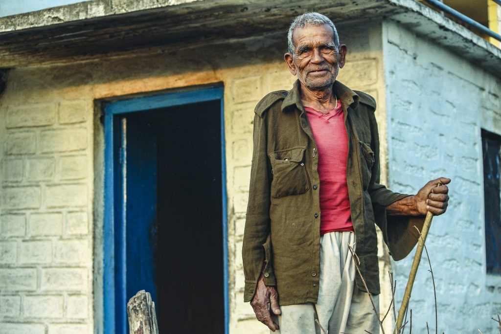 old man in front of house looking for work
